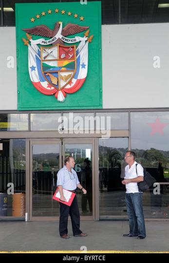 Panama Panama City Aeropuerto Tocumen airport PTY aviation terminal entrance door national shield man standing - Stock Image