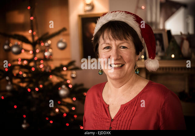 A woman by a Christmas tree wearing a Santa hat. - Stock Image
