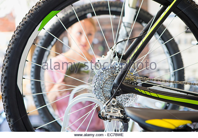 Female customer in shop choosing a bicycle - Stock Image