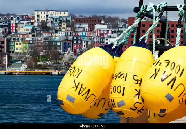 Yellow bouys with colorful city of St. John's, Avalon Peninsula, Newfoundland, Canada - Stock Image