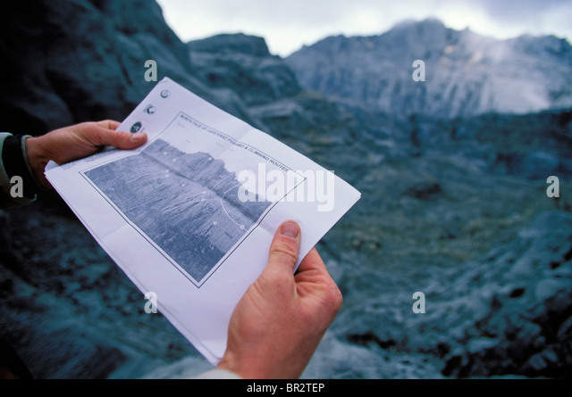 Hands holding up a topo map of climbing routes on a mountain in the background. - Stock Image