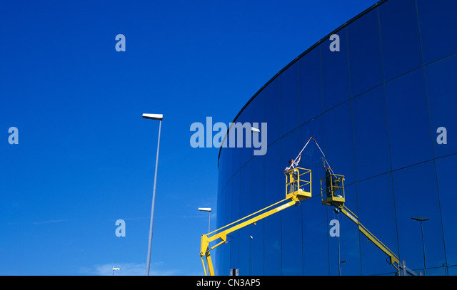 Person in access platform cleaning office window - Stock-Bilder