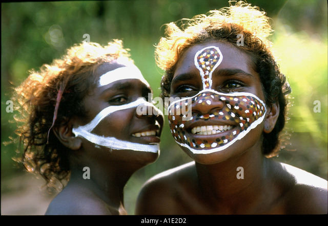 Aboriginal sisters Tessa and Jane enjoy painting their faces with their clan motives and totems at remote Ramingining - Stock-Bilder
