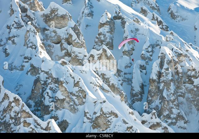 A Paraglider pilot flying past a stunning mountain rock formation. - Stock-Bilder