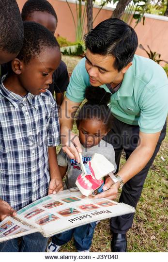 Miami Florida Liberty City Jessie Trice Community Health Center free care exam Asian Black man boy girl child professional - Stock Image