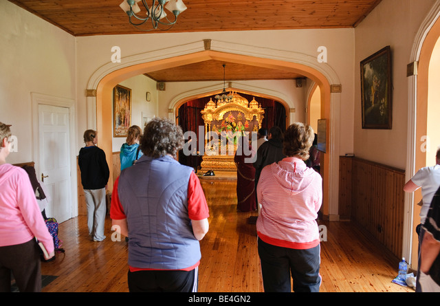 Devotees dance and chant at an altar in a Hare Krishna temple room - Stock Image