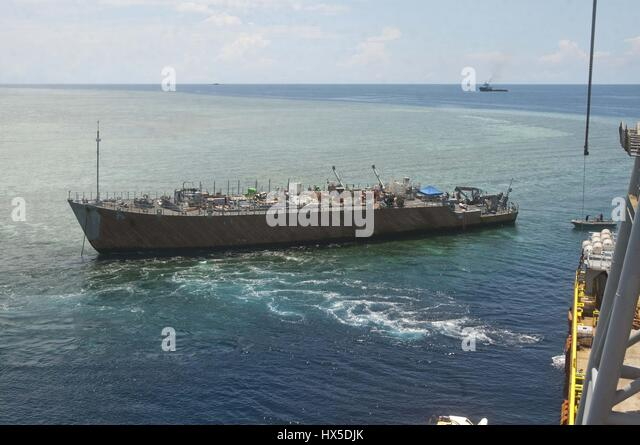 U.S. Navy and contracted salvage teams asses damage and prepare to salvage U.S. Navy mine countermeasures ship ex - Stock Image