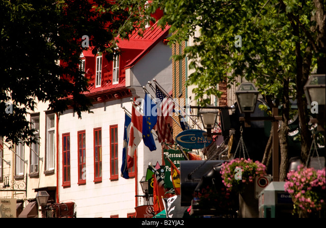 Street scene in historic old Quebec city showing French architecture, red roof, flowers and flags with open copy - Stock Image