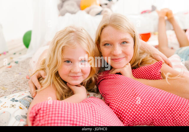 Portrait of smiling Middle Eastern sisters laying on floor - Stock Image