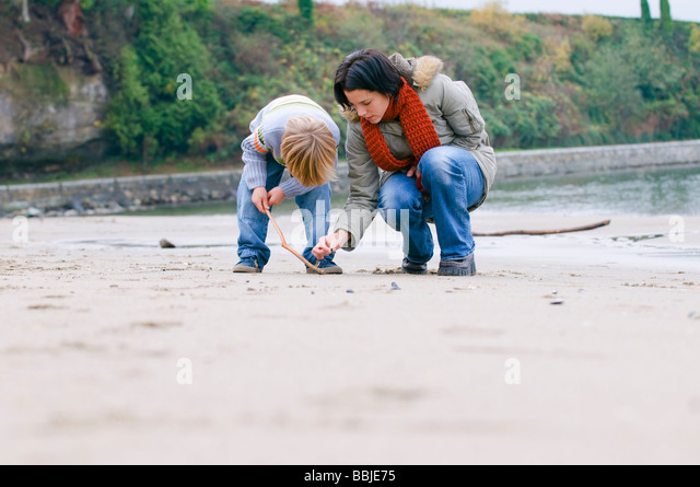 Woman and boy examine objects on beach, Vancouver, British Columbia - Stock Image