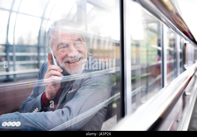 Senior man with smartphone in glass passage making phone call. - Stock Image