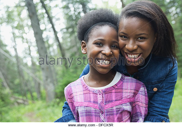 Portrait of happy sisters standing together in forest - Stock Image