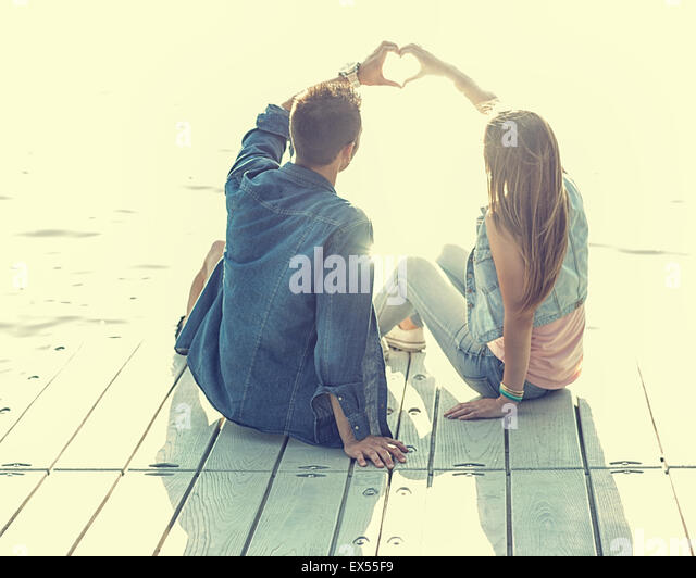 Couple in love sitting on the pier, their hands show heart - Stock-Bilder