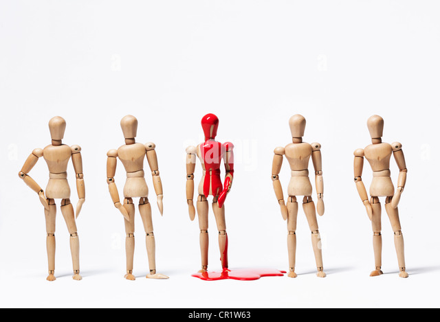 One wooden figurine in paint with others - Stock Image
