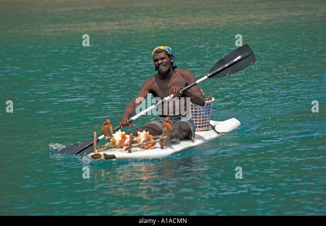 St Lucia  man paddling boat selling conch shells - Stock Image