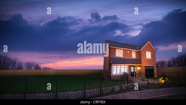 Brick house against sunset sky - Stock Image