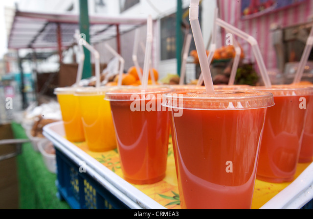 Close-up of fruit juices on display at market stall - Stock Image