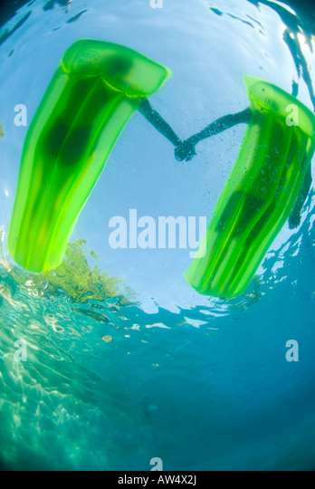 A couple on two green rafts holding hands shot from underwater - Stock Image