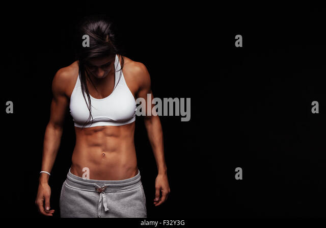 Image of fitness woman in sports clothing looking down. Young female model with muscular body. Horizontal studio - Stock-Bilder