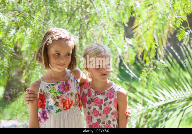 Candid portrait of two girls looking away in garden - Stock Image