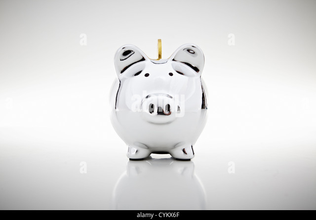 Gold coin dropping into piggy bank - Stock Image