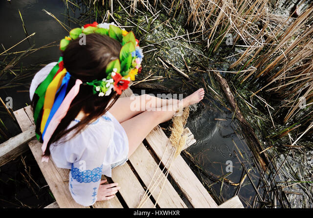 girl wets feet in the river. girl sitting on the bridge in the U - Stock Image