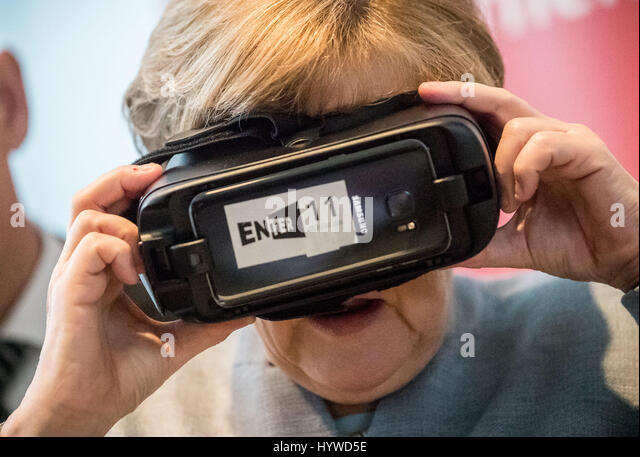 Berlin, Germany. 26th Apr, 2017. German Chancellor Angela Merkel (CDU) puts on VR glasses during the opening event - Stock Image