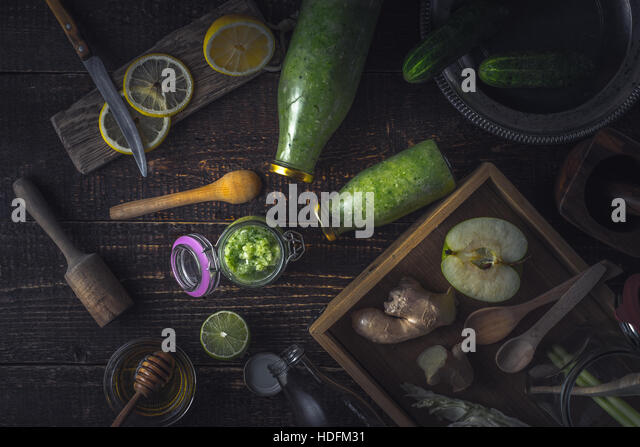 Bottles  and jar with  green smoothie and different ingredients on the wooden tray top view - Stock Image