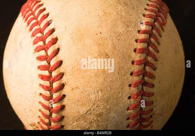 Close up of baseball showing red stitching - Stock Image