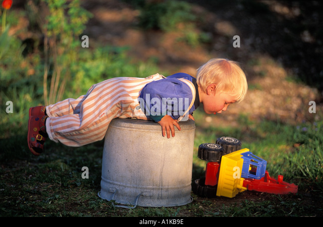 Two year old playing in the garden MR - Stock Image