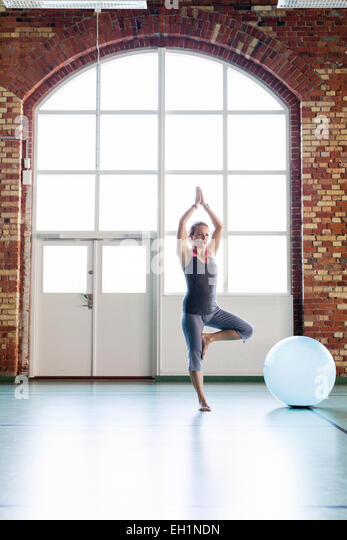 Full length of woman in tree position in health club - Stock Image