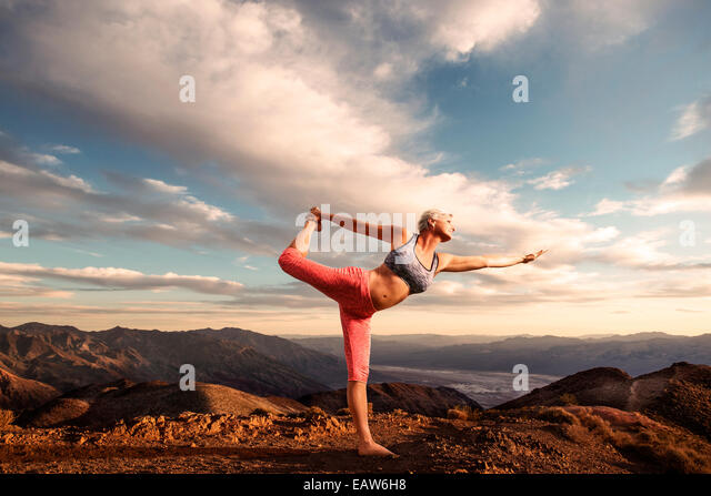 Senior woman doing yoga pose on top of mountain at sunset with landscape and desert valley below. - Stock-Bilder