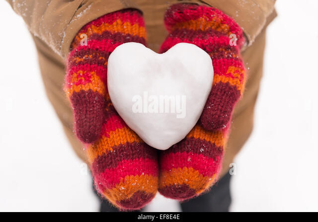 Woman in red mittens holding a heart made of snow, closeup of hands, romantic concept - Stock Image