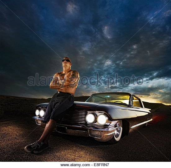 Tattooed man leaning against his vintage car - Stock Image