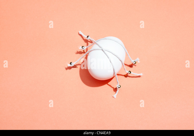 Egg tied to pink background with string - Stock Image