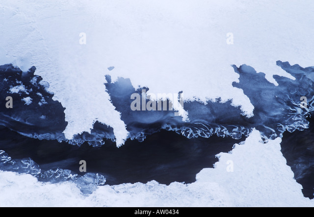 Canada British Columbia rocky mountains ice and snow frame moving water in creek - Stock Image