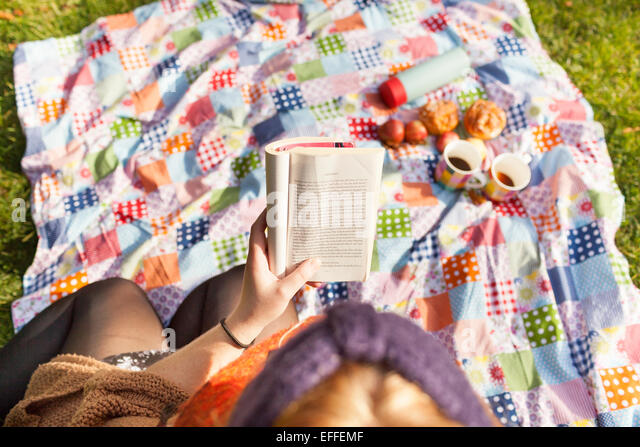 High angle view of young woman reading book on picnic blanket - Stock Image