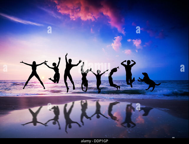 Happy people and dog jumping together on the sunset beach - Stock Image