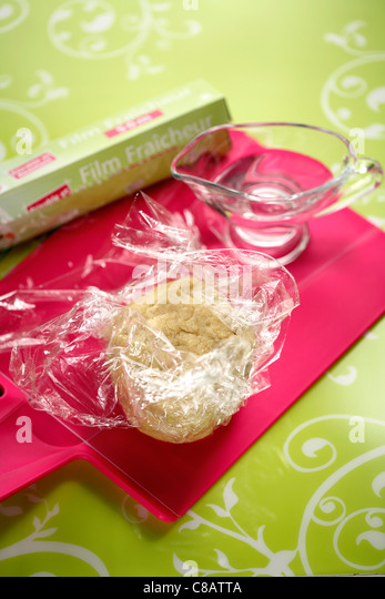 Wrapping the uncooked pastry in clingfilm - Stock Image