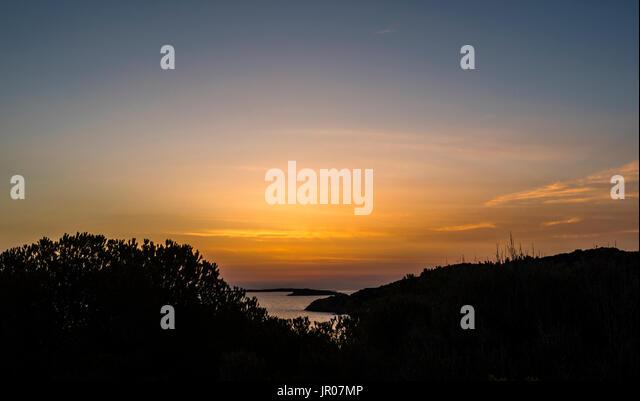 First light just before a fabulous orange sunrise over Sardinia, Italy - Stock Image
