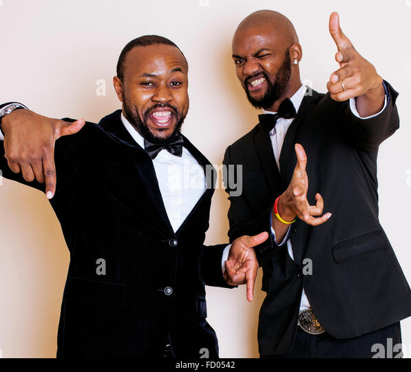 two afro-american businessmen in black suits emotional posing, gesturing, smiling. wearing bow-ties - Stock-Bilder