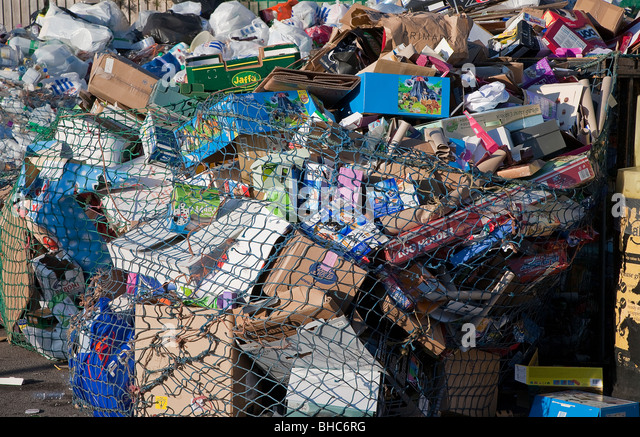 Close-up of cardboard waste in plastic net at recycling collection station in car par UK - Stock Image
