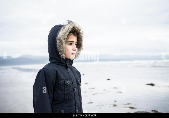 A young boy standing on the beach at Porthmadog. - Stock Image