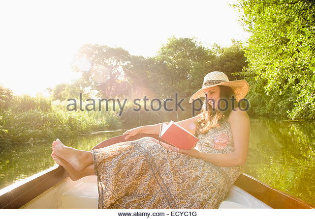 Hispanic woman reading in canoe on river - Stock Image