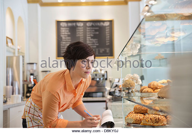 Female small business owner taking inventory in coffee shop - Stock-Bilder