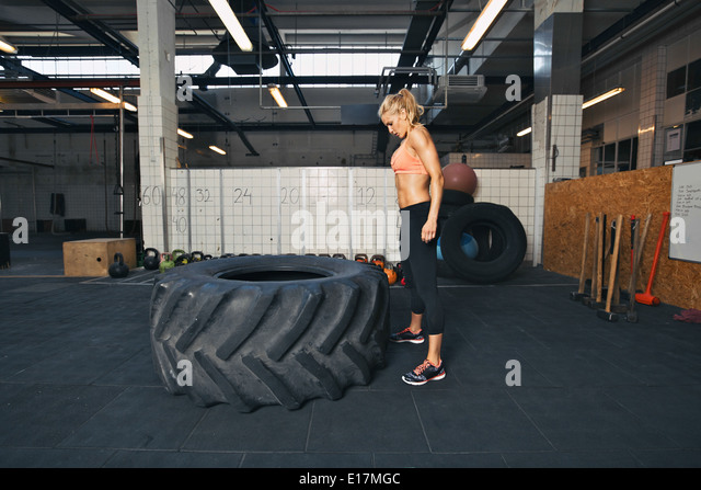 Strong young woman athlete standing and looking at huge tire at gym. Fit female athlete performing tire flipping - Stock Image