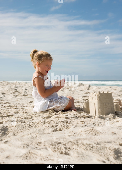 Happy girl with sandcastle - Stock Image
