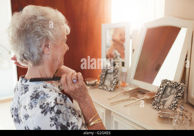 Happy senior woman combing her hair at dresser in house. Elderly female getting ready in front of a mirror at home. - Stock Image