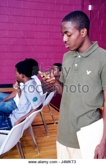 Miami Florida Overtown Overtown Youth Center Summer Career Training Program student teen audience Black boy texting - Stock Image