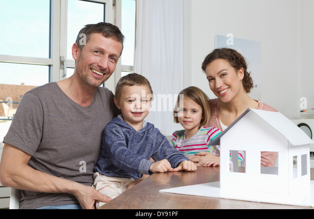 Family of four with house model - Stock Image
